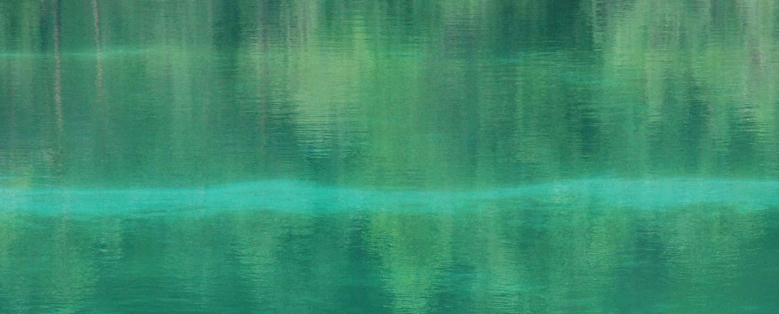 Intensiv türkisfarbige Oberfläche eines Sees, in dem sich verschwommen Bäume spiegeln, die man aber nicht direkt sieht
