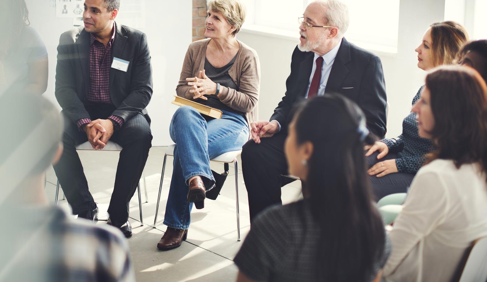 Im Kreis sitzende Teilnehmer eines Workshops